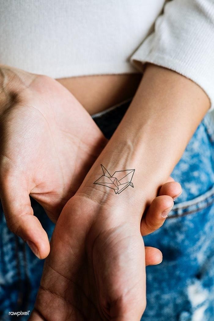 Kleines Origami Tattoo am Handgelenk, coole Tattoos für Hand, Jeans und weiße Bluse