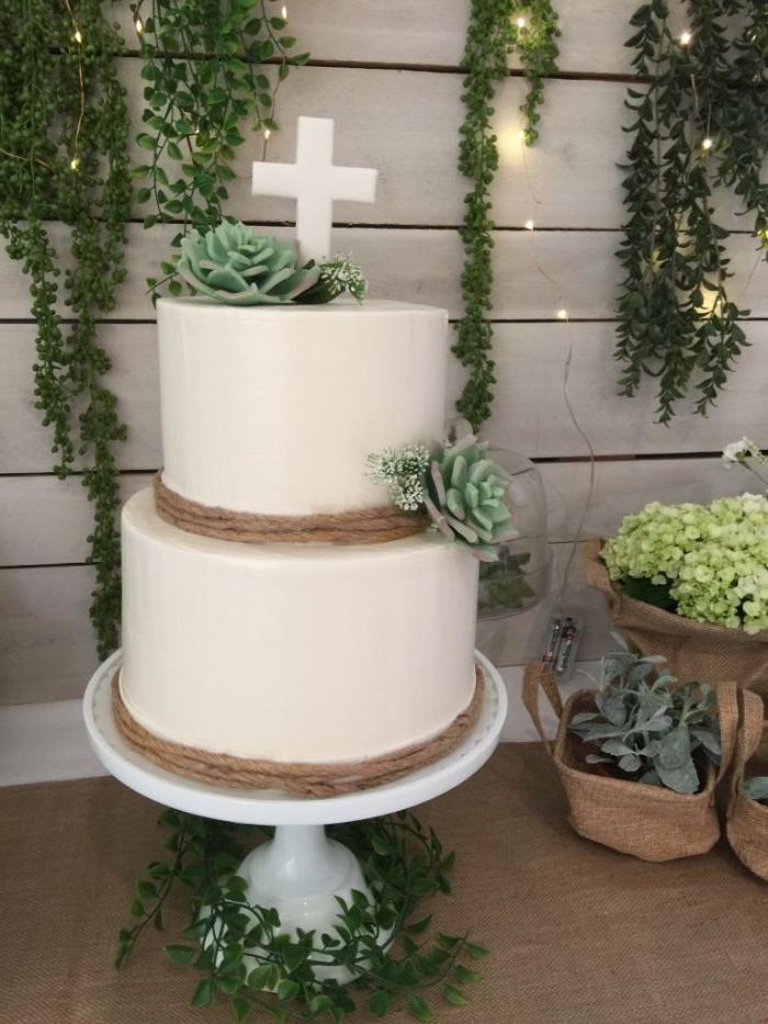 deko taufe junge, eine große zweistöckige torte mit deko kreuz und natürlichen blumen