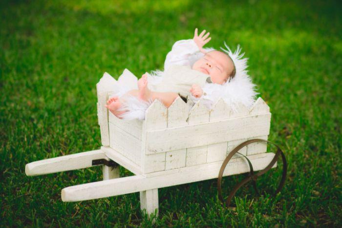 taufdeko ideen baby liegt in einem weißen stück, garten deko und fotosession vom jungling