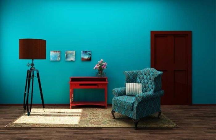 petrol farbe psychologie, petrolwand in einer blau türkis nuance, petrol details am sessel, rotes regal