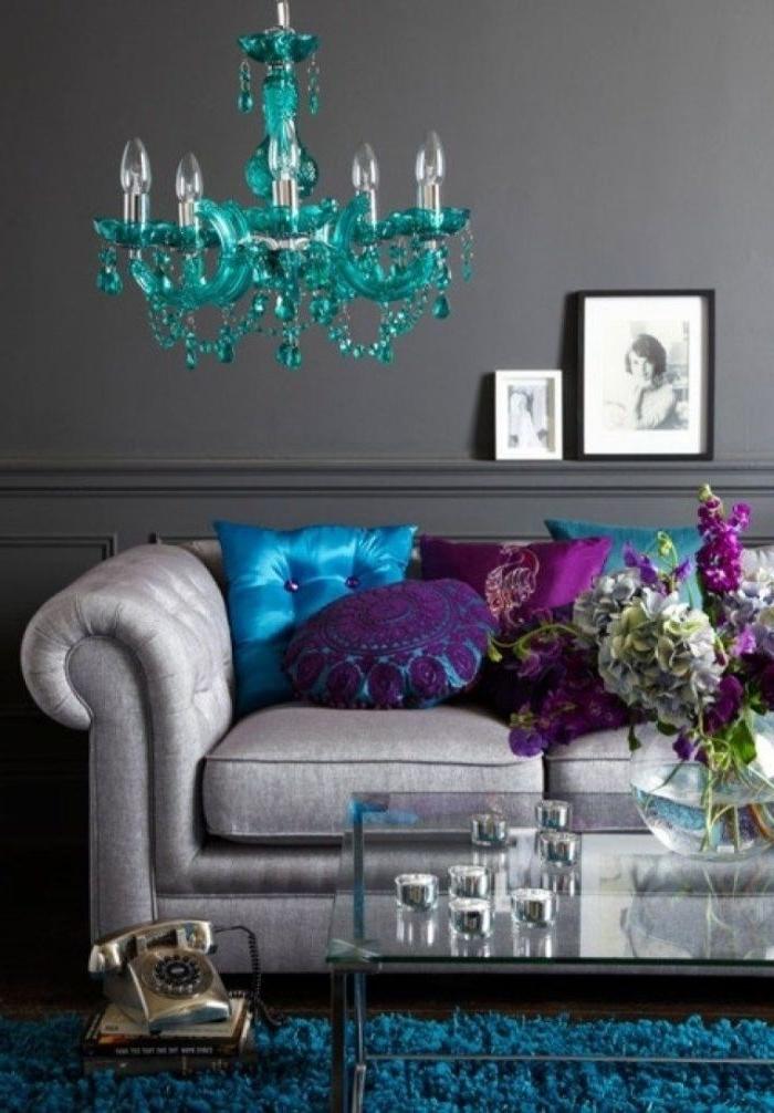 petrol farbe wohnzimmer, wohngestaltung, graues sofa, blaue kissen, lila deko, lüster türkis, bilder
