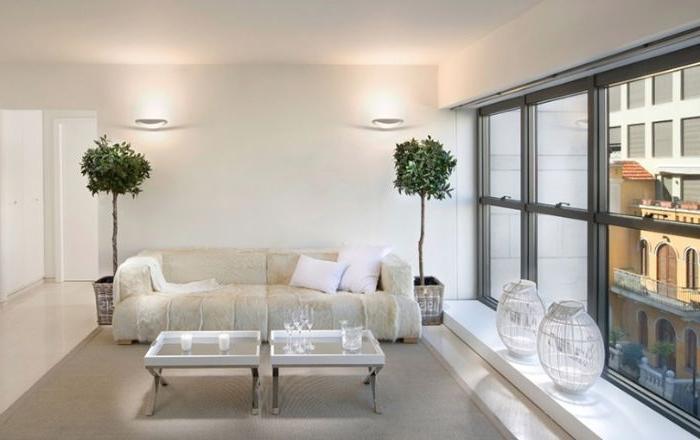 minimalistische möbel, dezentes champagner weiß sofa, zwei grüne pflanzen, vasen am fenster