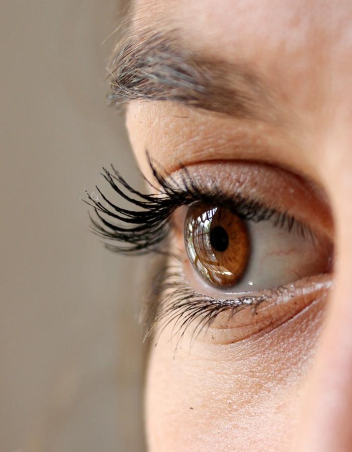 ein braunes Auge mit langen Wimpern, Wimpernserum zur Verlängerung der Wimpern