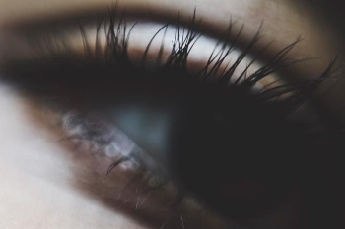 ein dunkles Auge mit langen Wimpern nach der Verwendung eines Wimpernserums