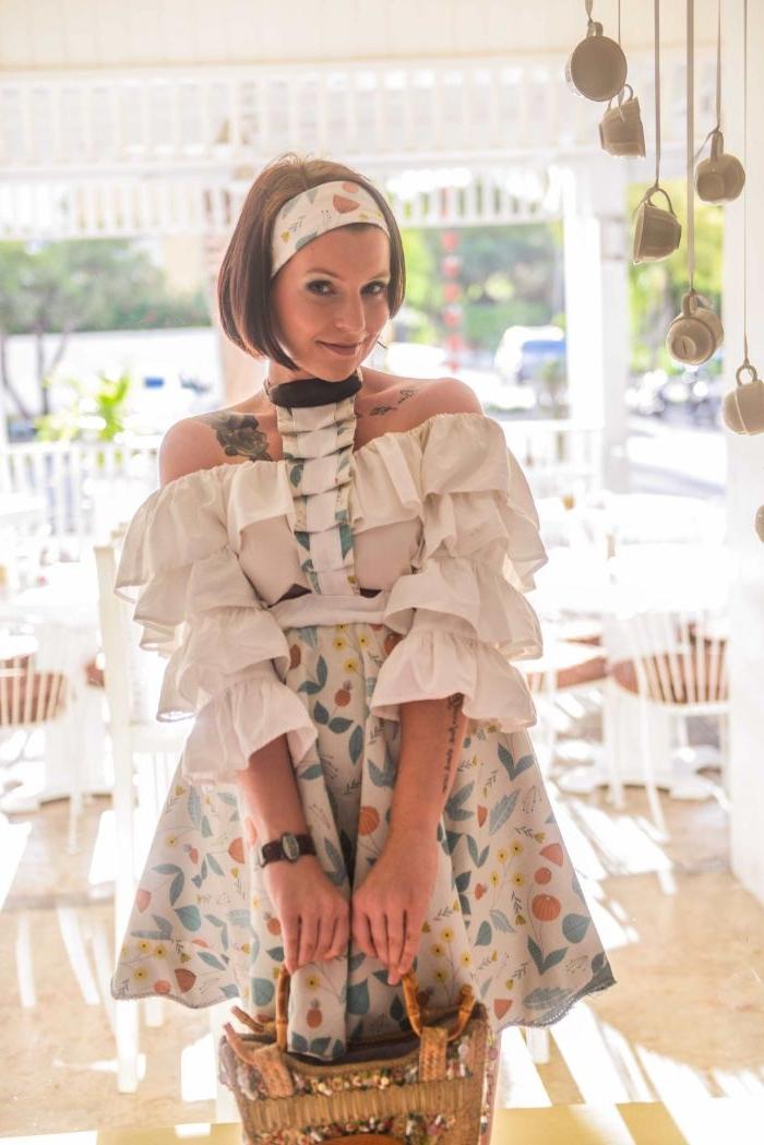 vegane kleidung, eine nette frau mit weißem oberteil und bunte röcke, kopfband, kurze glatte haare