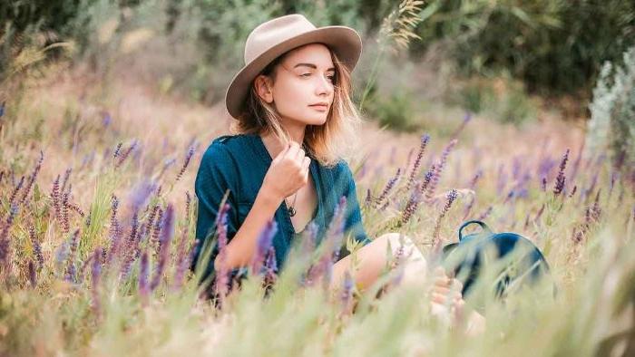 öko kleidung, eine schöne schlanke frau sitzt im gras auf dem boden mit einem hut, naturfreundlich leben