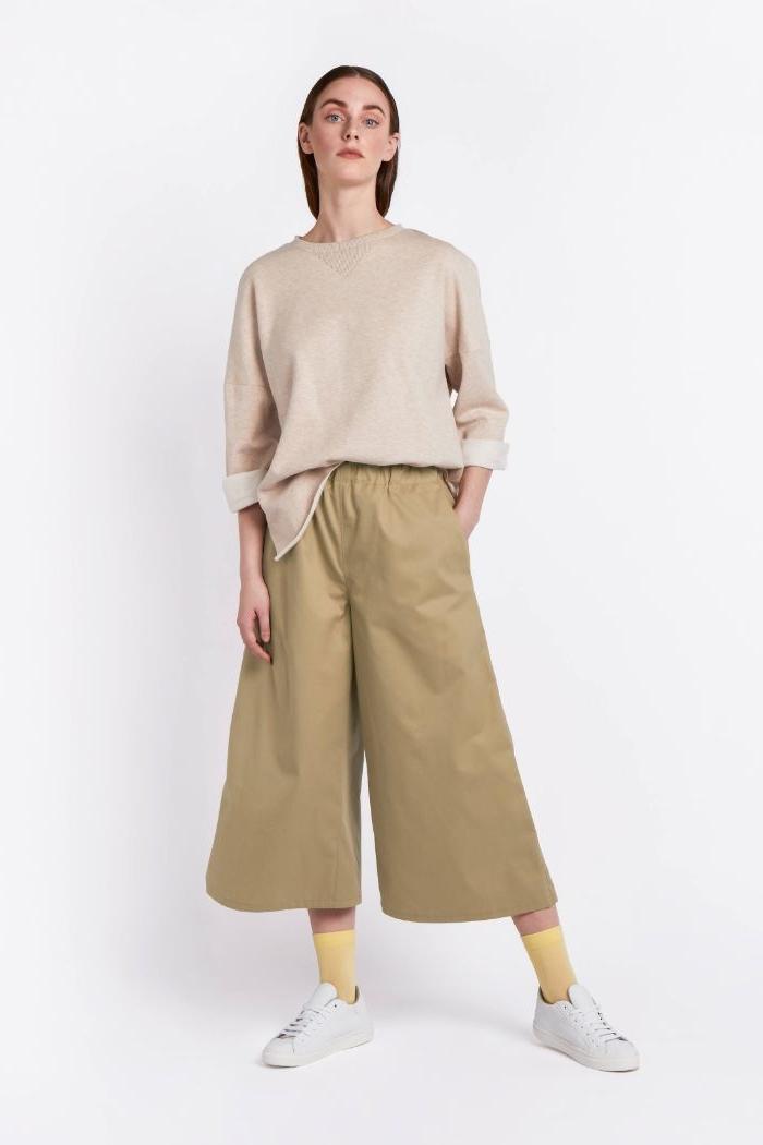 öko kleidung, eine frau in neutralem outfit, kleidung breit und bequem, beiger pulli, beige hose, weiße sneakers