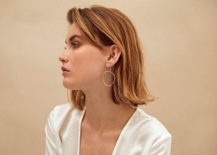 öko mode, eine frau im profil fotografieren, mittellanges haar, ohrringe, weißes oberteil
