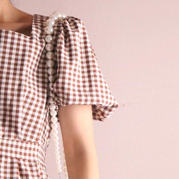 gatsby kleid, kariertes kleid mit perlentasche, perlen kette deko, weiß und braun