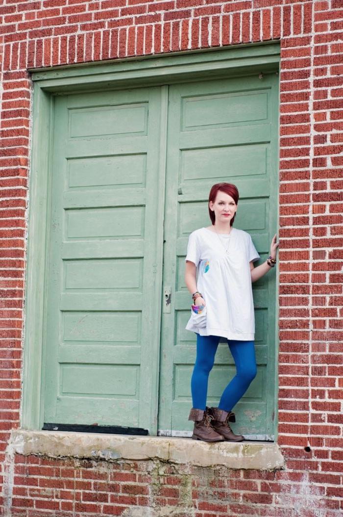 fair fashion, eine frau mit langem weißen oberteil, blaue jeggings hose, stiefel, foto an der wand