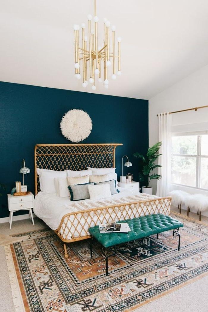 schlafzimmer ideen, eine dunkle wand, wandgestaltung idee, weiße pompons, bett mit goldenem rahmen, grünes sofa, persischer teppich, traumteppich
