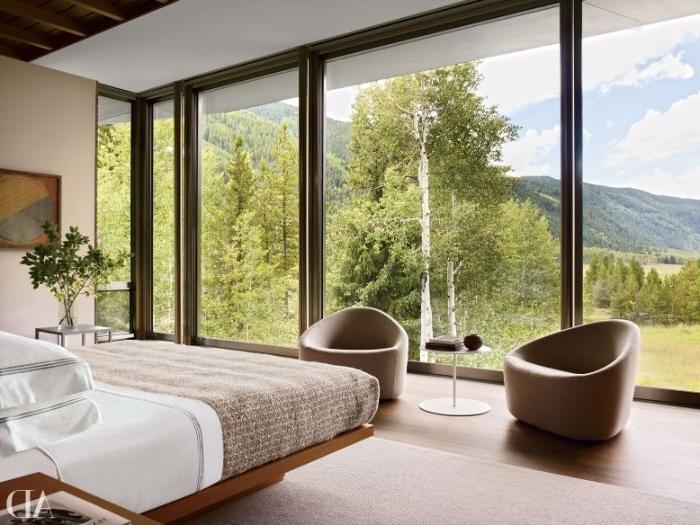 zimmer einrichten, schönes hotelzimmer mit einem faszinierenden ausblick in die natur, doppelbett, zwei sessel mit kaffeetisch