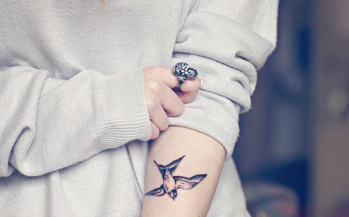 Ideen für Vögel Tattoos, kleine Schwalbe am Unterarm, Symbol für Freiheit, weißer Pullover, massiver Ring am Mittelfinger