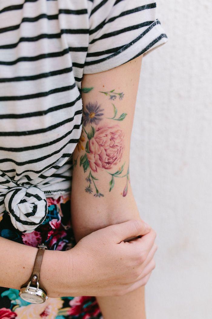 Farbiges Blumen Tattoo am Oberarm, gestreifte Bluse in Weiß und Schwarz, Rock mit Blumenmuster