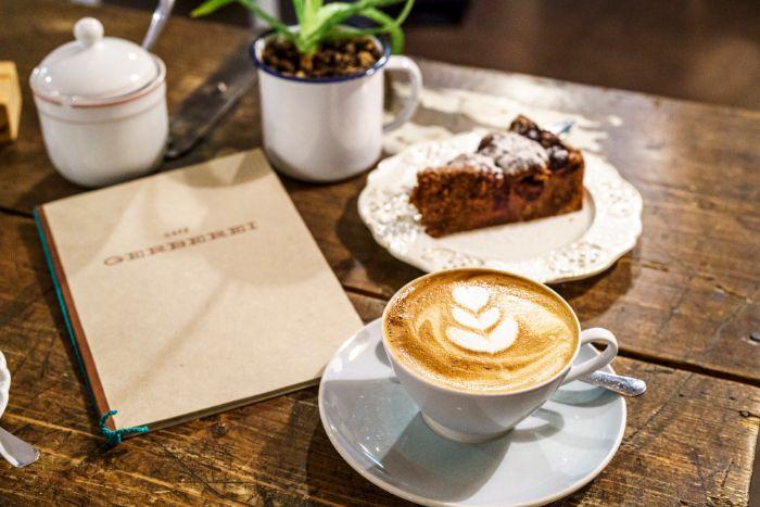 linzer torte, ein schönes foto vom tisch mit cappucchino und torte, plus pflanze in einer tasse als deko