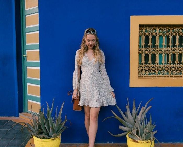nachhaltige mode, schöne junge frau mit langen weißen haaren und einem kurzen kleid, blaue wand, fenster