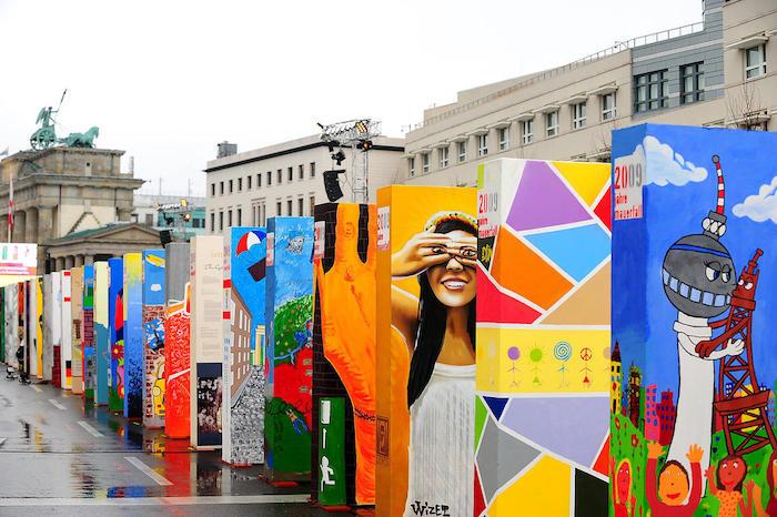 viele große bunte dominosteine mit bildern in berlin, brandenburger tor, jubiläum des mauerfalls, bilm mit einer frau