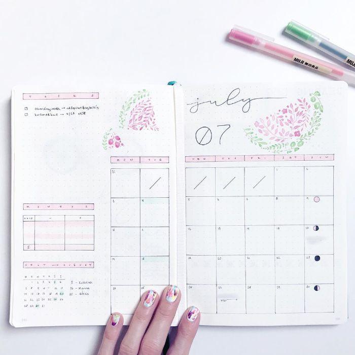 bullet journal zubehör, bunte stifte liegen auf dem schreibtisch neben ein weißes heft, kalender selber machen