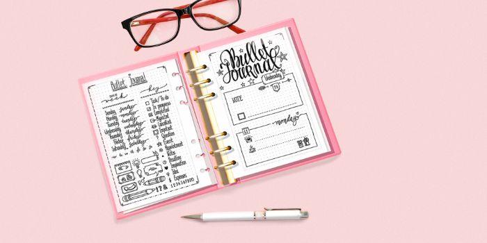 bullet journal deutsch ideen, rosaroter hintergrund, rosa wandbild, brille, ein heft mit ideen