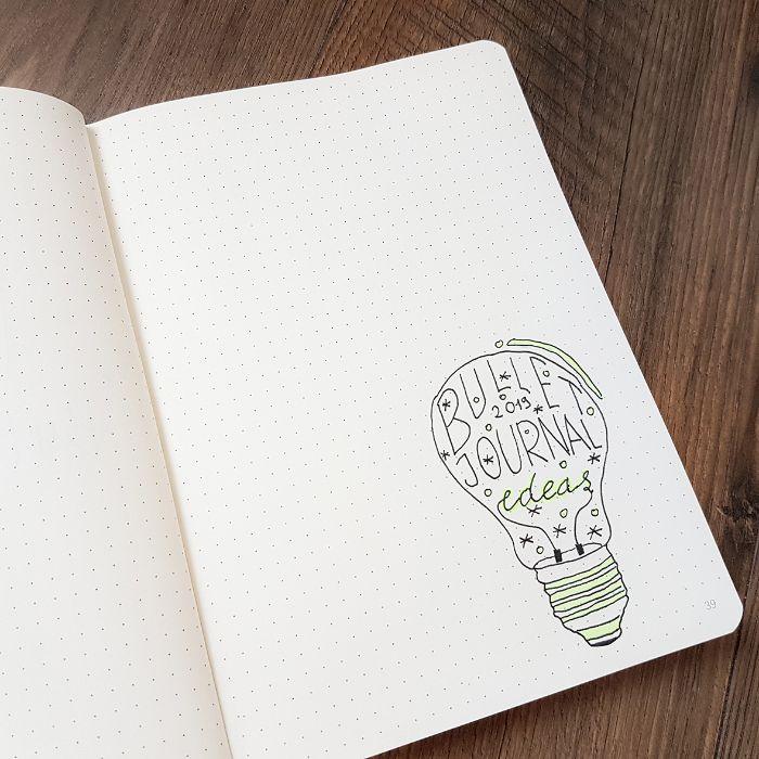 bullet journal anfänger, weißes heft mit minimalistischer designer deko eine glühbirne mit aufschrift darauf