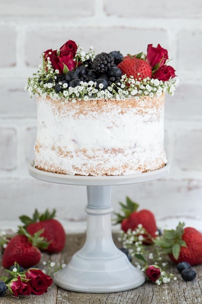 cake mit füllung aus weißer sahne dekoriert mit kleinen blpten und waldfrüchten