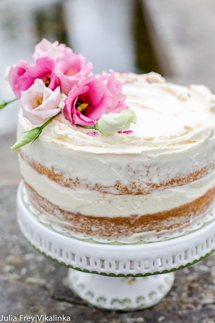 cake mit füllung, torte mit vanilleboden und sahne dekoriert mit rosa blüten, geburtstagskuchen