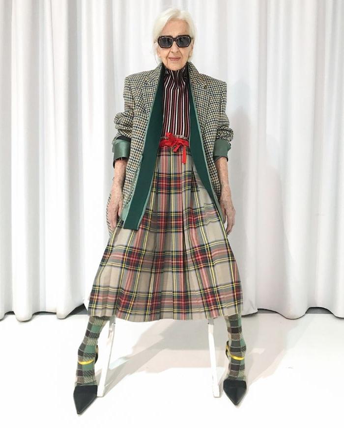 skandinavische mode für jedes alter, eine alte dame, super trendy, karriertes outfit mit rock, hemd, weste und absatzschuhen mit strumpfhosen