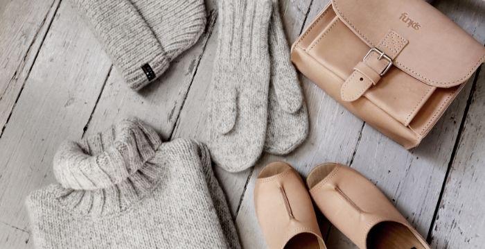 skandinavische mode, eine beige tasche mit schuhen in der selben farbe, grauer pulli, handschuhe, hut