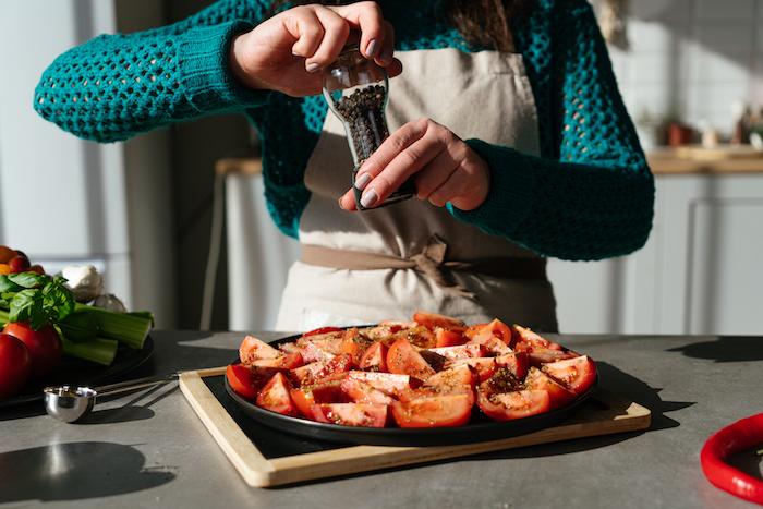Tomatensuppe Rezept, Tomatenstücke mit getrocknetem Oregano und schwarzem Pfeffer würzen