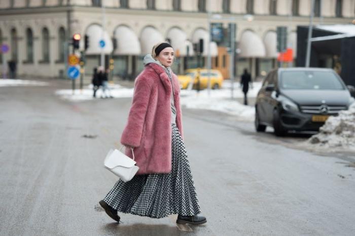skandinavische mode für jede saison, eine frau mit langem rock mit plisseen, rosa flauschiger mantel