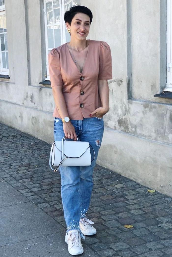 französische mode, casual look jeans mit perlen, eine bluse aus seide mit großen knöpfen und weiße tasche mit sneakers