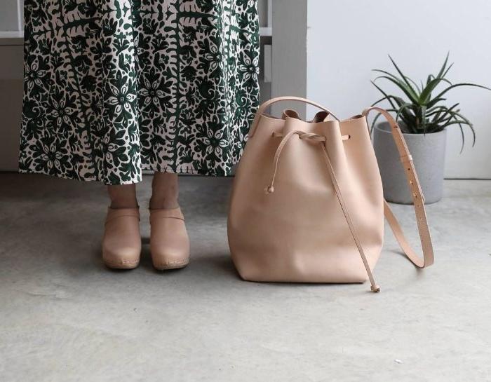 französische mode, beige tasche mit beigen schuhen und ein weißer rock mit grünen minimalistischen details