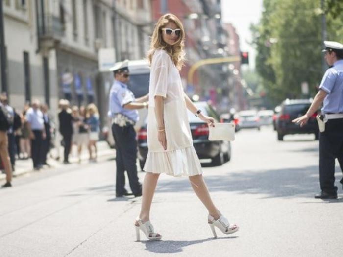 französische mode, weißes alltägliches kleid mit weißen absatzsandalen und brille in der selben farbe, ein foto auf der straße