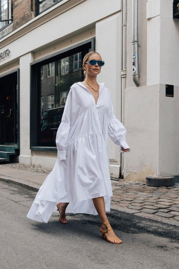 dänische mode, eien elegante frau mit hemdkleid mit langen ärmeln und nude farbe sandalen, cooler style für den sommer