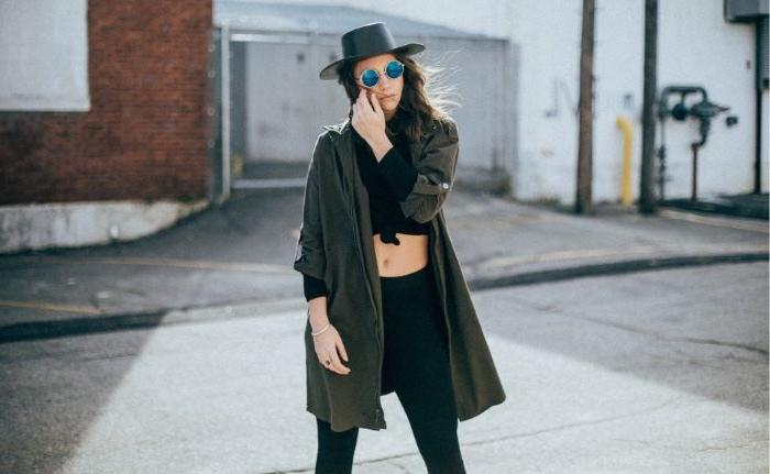 dänische mode große größen oberteil, eine frau mit sportlichem alltäglichen stil, schwarze jeggings, hut, brille, kurzer crop top