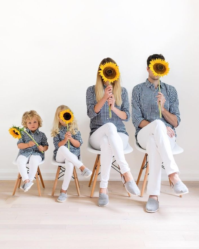 mode kataloge für die ganze familie, mama papa und die zwei kinder halten sonnenblumen, weiße hose, blaue hemde