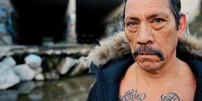 Danny Trejo mit zwei Tattos, eine schwarze Jacke, großer Schnurrbart, ein Wasserspiel