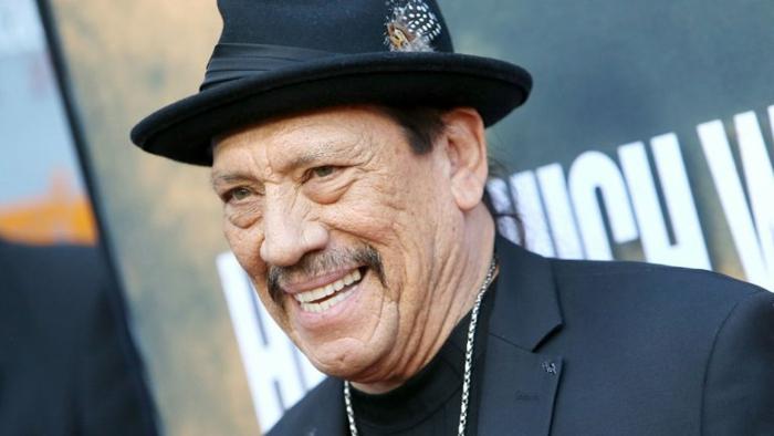 Danny Trejo, eine Kette, ein schwarzer Anzug und schwarzer Hut, ein Lächeln