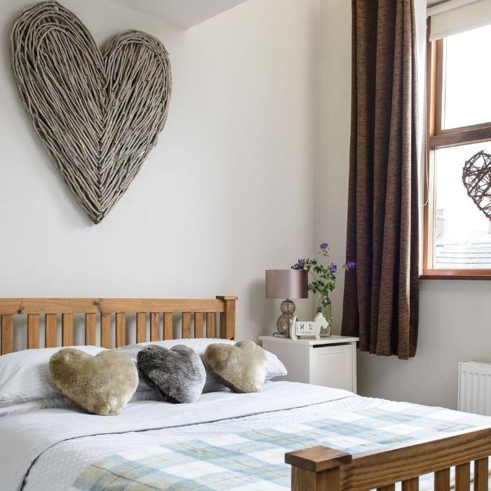 schlafzimmer einrichten, ein großes bett, herz deko an der wand, drei kleine herzchen dekorationen, doppelbett