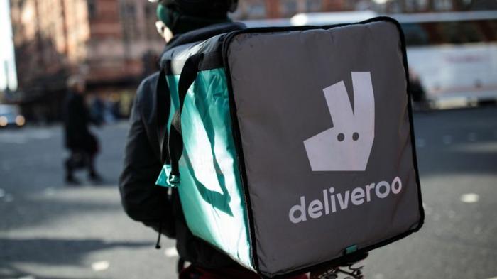 ein Fahrer mit dem Logo von Deliveroo mit weißem Buchstaben, grüne Tragetasche
