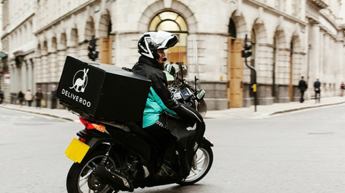 ein Deliveroo Fahrer in Berlin mit einer schwarzen Tasche und ein Mofa zu schneller Lieferung
