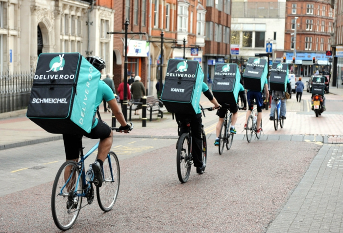 eine Reihe von Deliveroo Fahrer, die irgendwo gehen mit Fahrräder auf eine Straße
