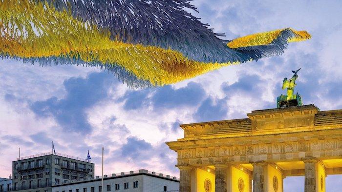 himmel mit vielen wolken, brandenburger tor in berlin, die kunstinstallation freiheitswolke mit vielen gelben und blauen zetteln mit wünschen