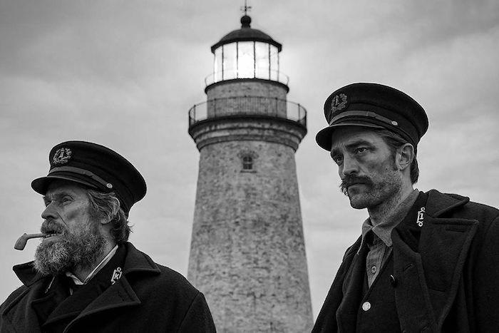 alter mann mit bart und mit einer pfeife, ein großer weißer leuchturm und ein grauer himmel mit wolken, der film the lighthouse
