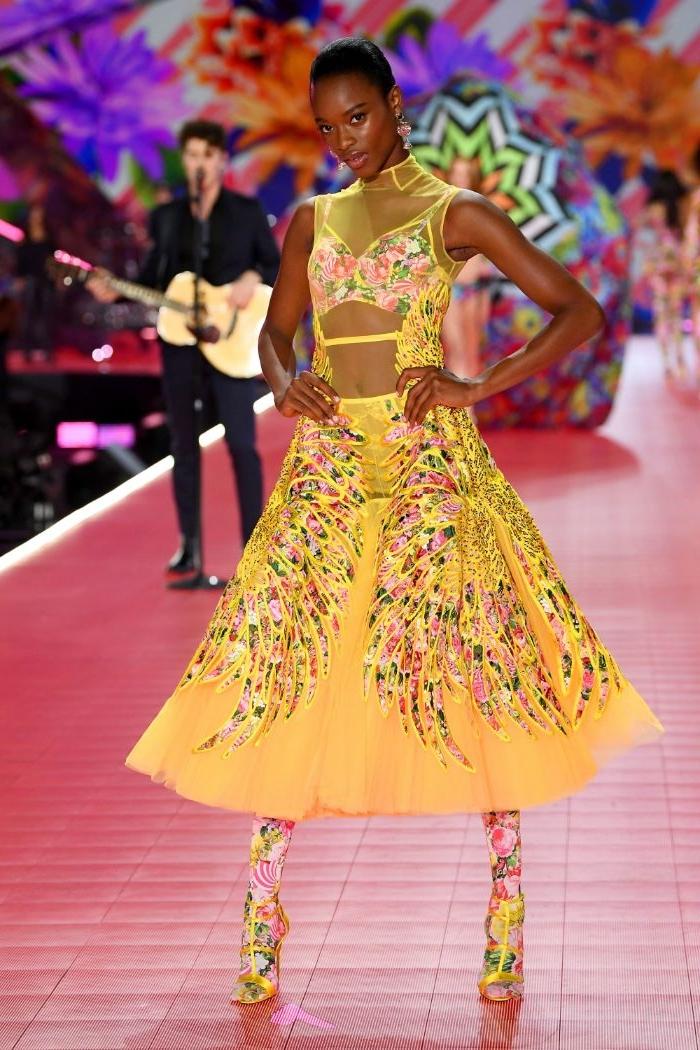 fair trade kleidung, gelbes kleid, eine schöne frau ist model bei einer show, absatzschuhe, transaprentes kleid