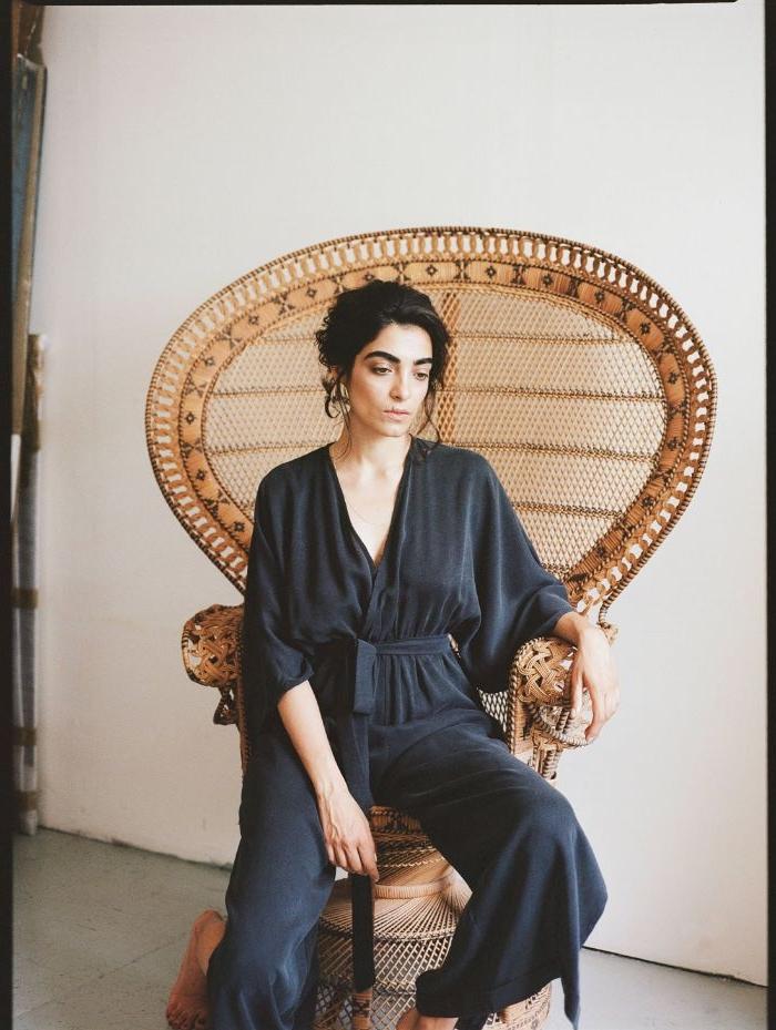 fair trade kleidung, eine frau sitzt im stuhl, tolle kleidung jumpsuit schwarz oder dunkelblau, ein stuhl aus rattan