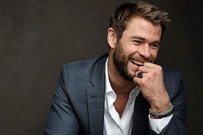 der schauspieler chris hemsworth, ein mann mit hand mit ring und armband und einem blauen kostüm und weißem hemd