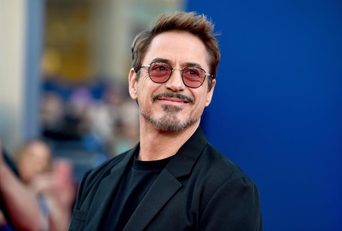 ein mann mit einem schwarzen anzug und brille und bart, der schauspieler robert downey jr