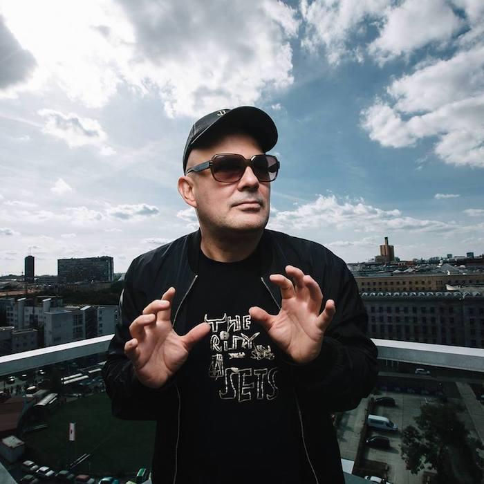 der techno dj westbam, ein mann mit hut und schwarzer brille und t-shirt, blauer himmel mit weißen wolken