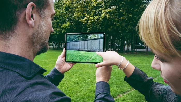 garten mit grünen bäumen und der berliner mauer, ein man und eine frau mit hand mit armband, ein tablet mit der neuen app mauAR, die die ehemalige berliner mauer zeigt
